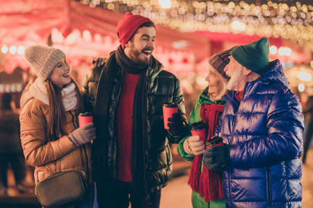 Photo of full family four members x-mas gathering hold mug drink eggnog share news have fun wear outerwear hat scarf coat gloves multi-generation night street park illumination fair outdoors