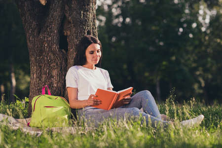 Portrait of her she nice attractive pretty lovely focused girl reading novel interesting book diary sitting on lawn green color grass veil duvet spending weekend pastime hobby