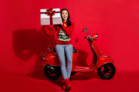 Full length body size view of her she nice attractive glad cheerful girl sitting on moped holding in hand big large giftbox st nicholas day isolated bright vivid shine vibrant red color background