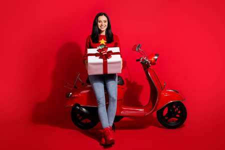 Portrait of her she nice attractive glad cheerful cheery girl sitting on moped holding in hands big large bow ribbon giftbox isolated bright vivid shine vibrant red color background