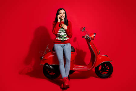Portrait of her she nice attractive lovely glad cheerful cheery girl sitting on moped calling friend discussing news having fun laughing isolated bright vivid shine vibrant red color background