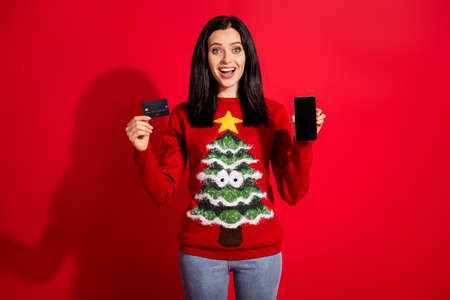 Portrait of her she nice attractive glad cheerful cheery girl holding in hand plastic bank card gadget use app buy delivery fast shipping isolated bright vivid shine vibrant red color background