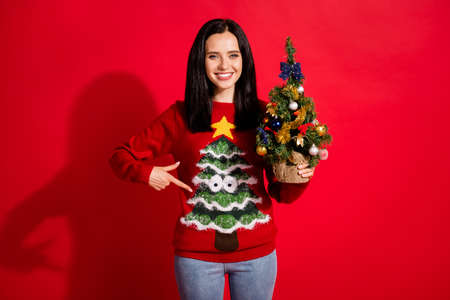 Portrait of her she nice attractive lovely pretty glad cheerful cheery girl holding in hand festal tree demonstrating wear ornament isolated bright vivid shine vibrant red color background