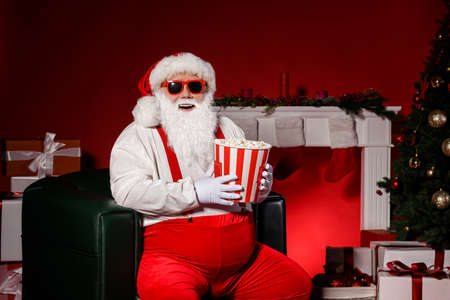 Photo of grey bearded santa claus sit in chair hold pop corn box with x-mas evergreen tree magic decoration isolated bright shine color background