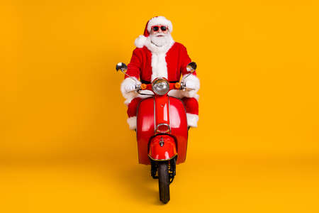 Portrait of his he nice funny fat confident Santa St Nicholas driving motor bike traveling way road wintertime sale discount congratulations isolated bright vivid shine vibrant yellow color background Stock Photo