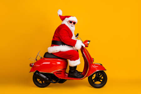 Profile side view of his he nice funny thick white-haired Santa riding motor bike fast speed hurry up rush sale hat ball fly race rally isolated bright vivid shine vibrant yellow color background