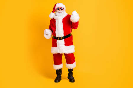 Full length body size view of his he nice funny cheerful cheery white-haired Santa St Nicholas having fun wearing winter warm look outfit isolated bright vivid shine vibrant yellow color background