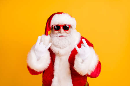 Close-up portrait of his he nice funny cool naughty white-haired Santa St Nicholas showing double horn sign heavy metal isolated over bright vivid shine vibrant yellow color background Stock Photo