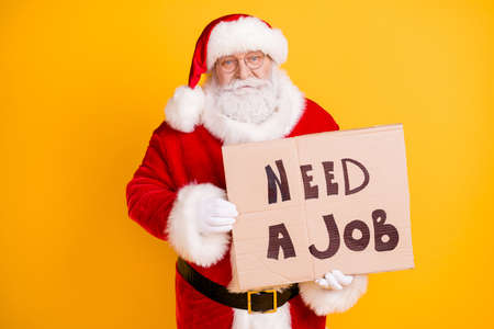 Portrait of nice frustrated white-haired Santa holding in hands paper card promo looking job industry crisis change occupation isolated bright vivid shine vibrant yellow color background 版權商用圖片