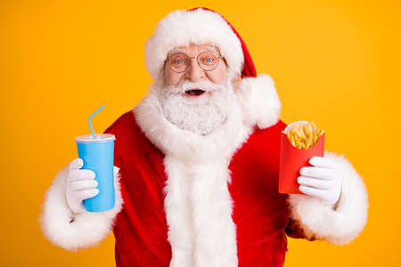Close-up portrait of his he nice cheerful cheery glad funny white-haired Santa enjoying eating fastfood menu meal drinking cola isolated over bright vivid shine vibrant yellow color background