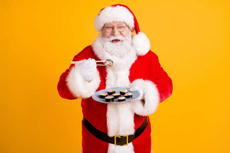 Portrait of nice cheerful white-haired Santa enjoying eating domestic gourmet sushi roll maki lunch oriental cuisine isolated bright vivid shine vibrant yellow color background