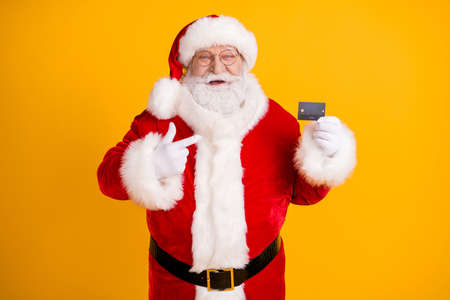 Photo fat white grey hair beard santa claus point finger credit card best choice x-mas eve noel christmas magic party purchase wear cap headwear isolated bright shine color background