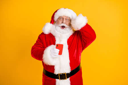 Oh no i send congratulations sms wrong x-mas christmas party. Amazed grey beard santa claus use smartphone touch cap hand wear red style costume isolated bright shine color background 免版税图像