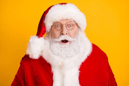 Close-up portrait of his he nice funny astonished amazed stunned wondered white-haired elderly Santa isolated over bright vivid shine vibrant yellow color bakcground
