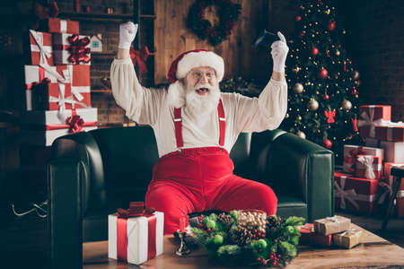 Photo of crazy addicted grey beard santa claus sit ouch have funny x-mas noel party play video game win raise fists wear red cap headwear in house indoors with christmas evergreen tree decoration