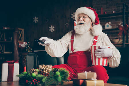 Photo of amazed grey beard santa claus sit couch watch x-mas christmas film movie eat pop corn box switch channel wear red cap bearded in house indoors noel ornament