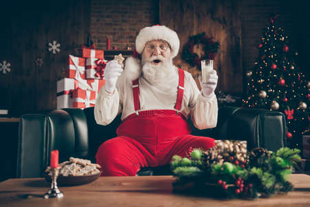 Shocked grey beard santa claus sit cozy couch watch x-mas christmas cinema film impressed drink milk glass eat gingerbread cookie wear red cap headwear in house indoors noel ornament