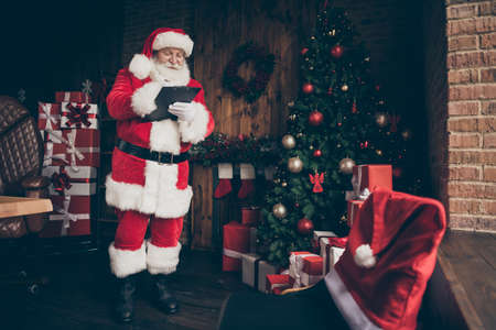 Full length photo white grey hair beard santa claus prepare x-mas christmas write clipboard organize dream present delivery midnight wear cap belt boots house indoors noel tinsles baubles