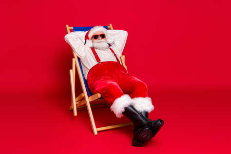 Portrait of his he nice handsome bearded Santa father hipster guy sitting in chair resting relax spending weekend free time leisure isolated bright vivid shine vibrant red color background