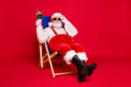 Portrait of his he nice handsome cheery bearded fat Santa father hipster guy sitting in chair relax chill out spending weekend leisure isolated bright vivid shine vibrant red color background