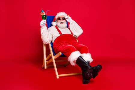 Portrait of his he nice handsome cheerful cheery glad bearded fat Santa father hipster sitting in chair chill out drinking mojito having fun isolated bright vivid shine vibrant red color background Stock Photo