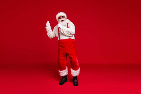Full length body size view of his he handsome cheerful cheery glad bearded Santa father hipster dancing having fun christmastime celebratory isolated bright vivid shine vibrant red color background Stock Photo