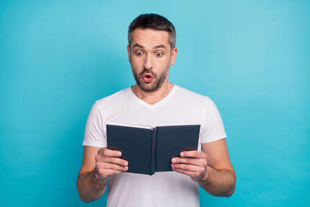 Close-up portrait of his he nice attractive cheerful cheery amazed bearded guy reading interesting book isolated over bright vivid shine vibrant blue color background