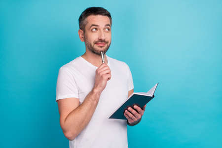 Close-up portrait of his he nice attractive cheerful cheery dreamy bearded guy holding in hand copybook creating strategy isolated over bright vivid shine vibrant blue color background