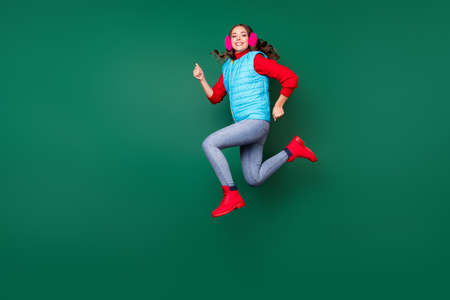 Full length body size view of her she nice attractive pretty lovely cheerful cheery active girl jumping running wearing casual season coat isolated over green pastel color background Stock Photo