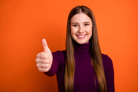 Photo of positive girl show thumbup sign feedback recommend suggest select ideal perfect ads promo wear winter purple jumper isolated over bright shine color background