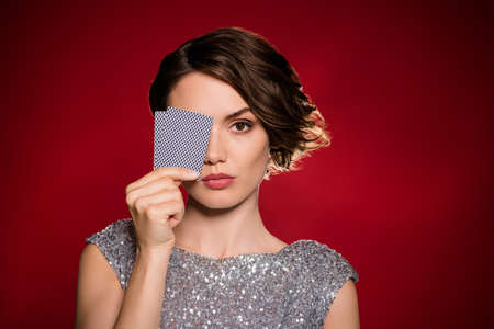 Closeup photo of attractive lady professional casino player hiding eye hold two deck play cards risky gamer all in bluffing wear shine dress isolated dark red gradient color background