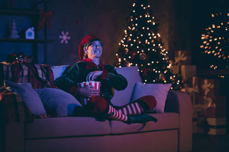 Full length photo of funky elf sit cozy couch watch movie eat pop corn from box in house indoors christmas x-mas evening illumination