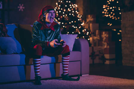 Full size photo of addicted elf sit comfort couch play video game in house indoors with christmas x-mas decoration night lights