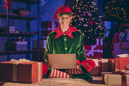 Full length photo of elf sit floor type greeting on laptop wear green glasses cap in house indoors with evening x-mas decor lights Stockfoto