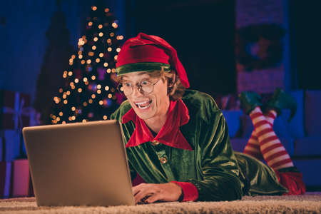 Shocked crazy elf read x-mas congratulation on laptop floor wear green costume in christmas evening house indoors with illumination