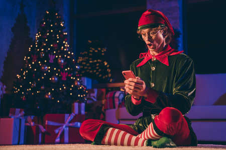 Full size photo of amazed elf sit floor read x-mas news on cellphone in house indoors with christmas evening illumination wear green cap