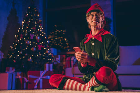 Full length photo of funky elf sit floor have smartphone wear green hat in house indoors with christmas evening x-mas fairy lights