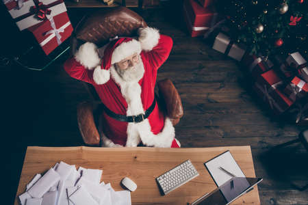 Top above high angle view photo grey beard santa claus finish organise wish list letters sit table armchair stretch hands wear costume in lapland polar house indoors x-mas christmas ornament Stockfoto