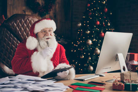 Grey beard thoughtful santa claus sit table work check wish list letters x-mas christmas event write clipboard think thoughts wear cap headwear in lapland house indoors with decoration