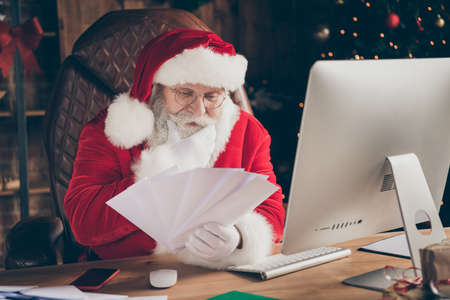 Photo of focused santa claus christmas worker want prepare gift present x-mas night midnight read wish list letters envelope touch grey beard think in house indoors with decoration