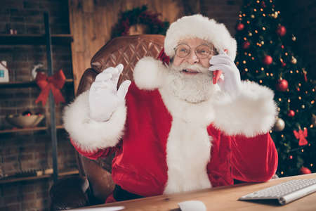Listen i have x-mas party ideas. Jolly holly white grey hair beard santa claus sit table call smartphone elf tell say christmas news wear cap headwear in house indoors with decoration lights