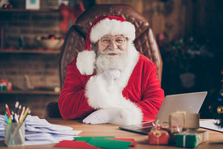 Portrait of positive fairy dream santa claus sit table in x-mas christmas newyear ornament tinsel house indoors touch beard ready answer wish list letter Stockfoto
