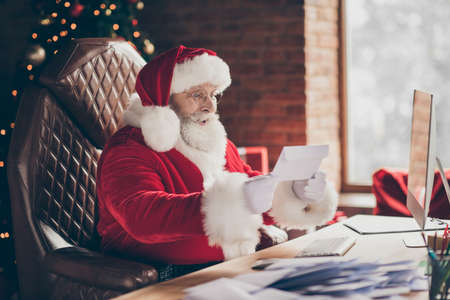 Profile side photo excited grey hair santa claus sit table impressed get wish list letter x-mas miracle fair christmas noel celebration wear red cap in house indoors with newyear decoration Stockfoto