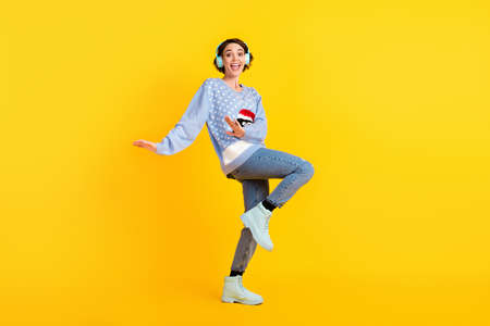 Full body profile photo of attractive crazy lady party newyear discotheque listen cool earphones dance floor night club wear ugly ornament sweater jeans shoes isolated yellow color background