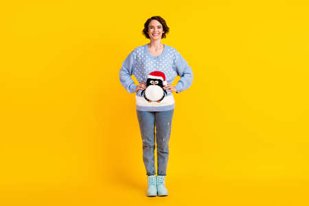 Full length photo of pretty funny lady try on new jumper cute fluffy penguin look mirror ready newyear family meeting party wear ornament sweater jeans boots isolated yellow color background
