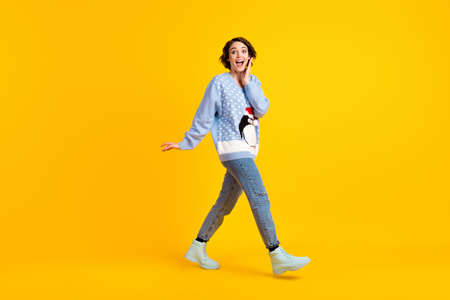 Full size profile photo of pretty funny excited lady walking x-mas party new jumper funky cute fluffy penguin wear ugly ornament sweater jeans boots isolated yellow color background