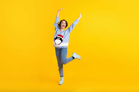 Full body photo of attractive lady x-mas party dance floor good mood greet friends raise hands arms wear penguin ugly ornament pullover jeans boots isolated yellow color background