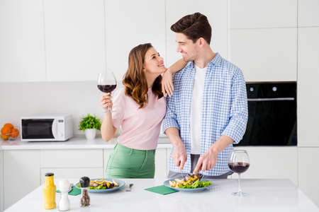 Two people affectionate bonding couple have 14-february celebration lunch man cut homemade frying beef barbecue girl touch his shoulders hold wine glass enjoy weekend i kitchen house indoors