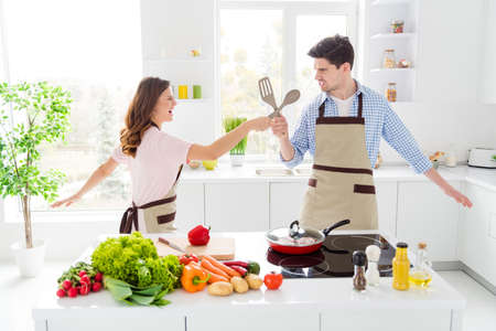 Portrait of two nice attractive positive funny cheerful cheery spouses cooking domestic homemade meal having fun fighting in light white interior kitchen house apartment indoors