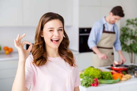 Excellent husband great chef. Two people enjoy hobby cook weekend man prepare raw meat beef dinner frying pan girl approve show okay sign wink in kitchen house indoors